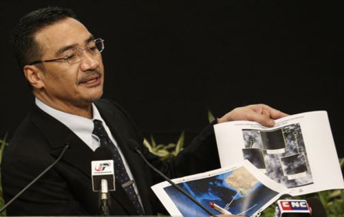 Malaysias acting Transport Minister Hishammuddin Hussein holds satellite images as he speaks about the search for flight MH370, during a news conference at Putra World Trade Center in Kuala Lumpur on March 26, 2014. /Reuters