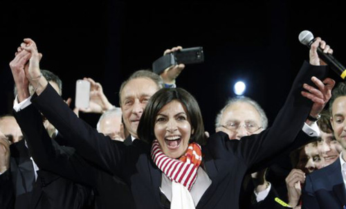French Socialist Party deputy mayor of Paris, Anne Hidalgo (center) smiles, as outgoing mayor Bertrand Delanoe, stands behind her, during a speech after results were announced in the second round of the French municipal elections in Paris on March 30, 2014. /AP