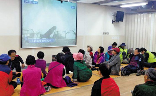 Residents of Baeknyeong Island watch TV news in a shelter on Monday.