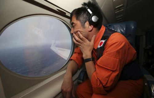 Koji Kubota of the Japan Coast Guard keeps watch while flying in the search zone for debris from flight MH370 on April 1, 2014. /AP