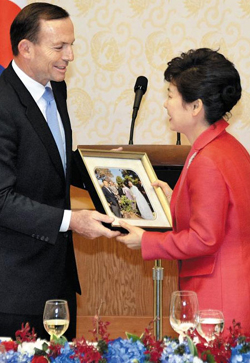 President Park Geun-hye (right) receives a photo of her 1968 visit to Australia along with her father, then-president Park Chung-hee, from Australian Prime Minister Tony Abbott at Cheong Wa Dae on Tuesday. /Newsis