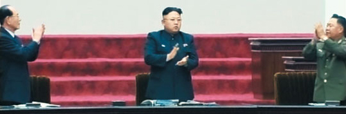Kim Jong-un (center) receives a standing ovation from ceremonial head of state Kim Yong-nam (left) and military politburo chief Choe Ryong-hae in Pyongyang on Wednesday. /[North] Korean Central TV