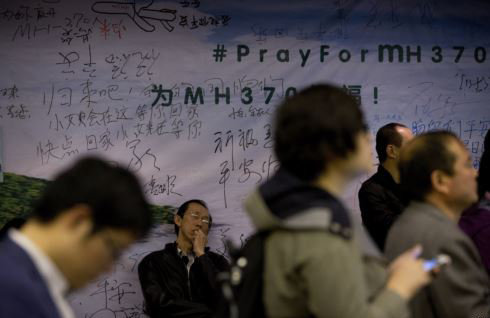A relative of Chinese passengers aboard Flight MH370 takes a nap against the wall displaying messages of wishes for the passengers during a briefing held by Malaysia officials at a hotel in Beijing on April 11, 2014. /AP