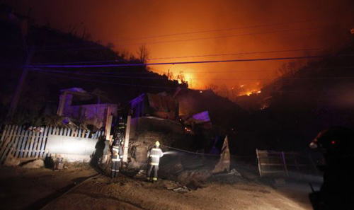 A group of firefighters stand next to destroyed homes as a forest fire rages towards urban areas in the city of Valparaiso, Chile on April 13, 2014. /AP