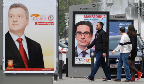 Young people pass beside boards with election posters of Gjorge Ivanov (left), current Macedonian President and a candidate of the ruling conservative VMRO-DPMNE party, with a slogan