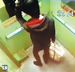 In this picture taken on Friday from CCTV camera in an elevator in Gumi, North Gyeongsang Province, a man looks himself in a mirror and tidies his hair, carrying a bag in which he is suspected to put his sons dead body. /Courtesy of Daegu Dongbu Police Station