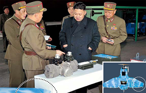 North Korean leader Kim Jong-un listens as officers show him equipment which appear to be drone engines, in this photo released by the [North] Korean News Agency on March 25, 2013. At the bottom left-hand corner is a part of a light-blue object (dotted) which appears to be the wing of a drone.