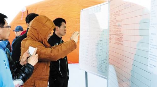 Family members of missing passengers look at the list of descriptions of newly found bodies from the sunken ferry Sewol at a port in Jindo, South Jeolla Province on Monday.