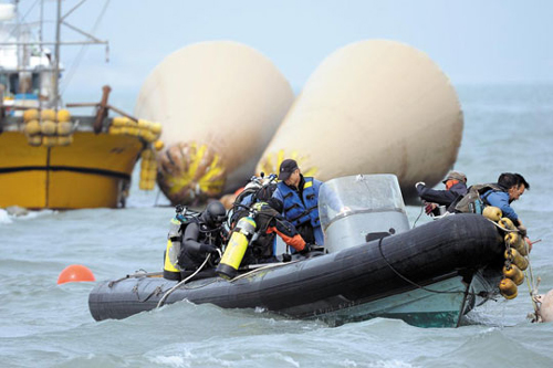 Divers search the wreck of the ferry Sewol in waters off Jindo, South Jeolla Province on Monday. /Newsis