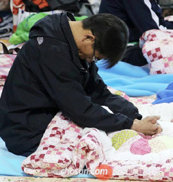 A relative of a missing passenger in the ferry disaster off the southwest coast hangs his head on Monday at a gymnasium in Jindo, South Jeolla Province, where the families of the victims are gathered.