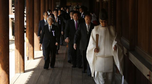 A group of lawmakers are led by a Shinto priest as they visit Yasukuni Shrine in Tokyo on April 22, 2014. /Reuters