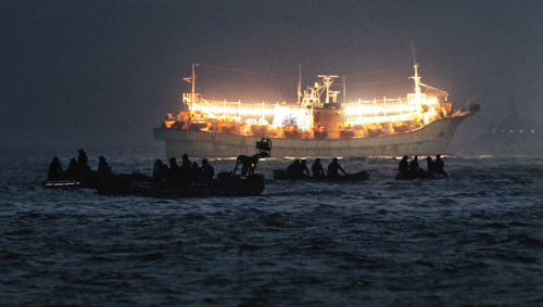 Rescue workers try to find missing passengers from the sunken ferry Sewol by the light of squid-fishing ships on Tuesday.