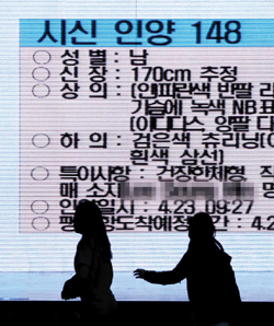 Families of ferry disaster victims hurry to a morgue after reading descriptions on an electronic board of a newly found body, at a gymnasium in Jindo, South Jeolla Province on Wednesday.