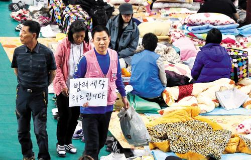 Volunteers collect laundry for families of missing passengers from the ferry Sewol at a gymnasium in Jindo, South Jeolla Province on Wednesday.