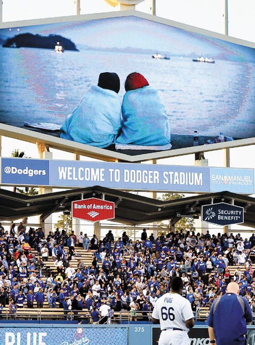 A banner showing two family members of a missing passenger sitting at a port in Jindo, South Jeolla Province is displayed at Dodger Stadium in Los Angeles on Wednesday.