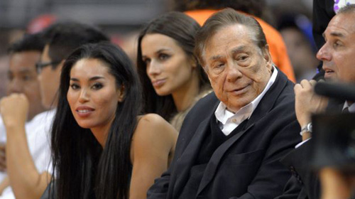 Los Angeles Clippers owner Donald Sterling (right) and V. Stiviano watch the Clippers play the Sacramento Kings during the first half of an NBA basketball game in Los Angeles (file photo). /AP