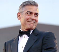 U.S. actor George Clooney smiles as he arrives on the red carpet for the premiere of