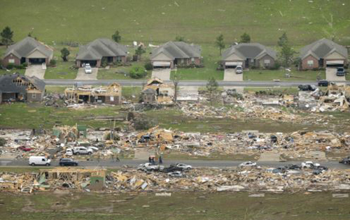 A row of lightly damages houses, top, face a row of destroyed homes after a tornado struck the town killing at least 16 people, Vilonia, Arkansas on April 28, 2014. /AP