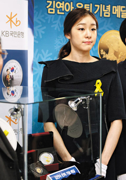 Figure skater Kim Yu-na poses with commemorative medals at a launch event in Seoul on Monday.