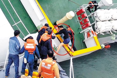 Lee Joon-seok (in red circle), the captain of the sinking ferry Sewol, escapes with the help of coast guards on April 16. /Newsis