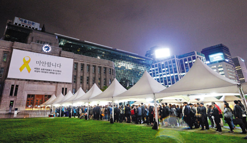 Visitors wait in line to mourn the victims of the ferry disaster in front of City Hall in Seoul on Monday evening. /News 1
