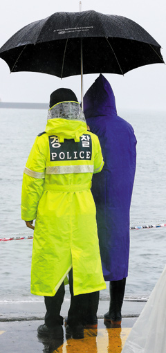 A policewoman shares her umbrella with the family member of a missing passenger from the ferry disaster in Jindo, South Jeolla Province on Monday.