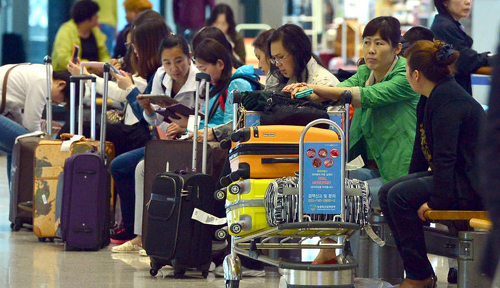 Foreign tourists wait at Incheon International Airport on Monday. /Newsis