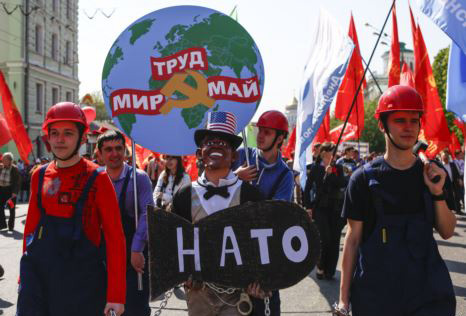 People in helmets dressed as Russian factory workers hold a man wearing a Barack Obama mask in chains as they take part in a Communists demonstration in downtown Moscow on May, 1, 2014. /AP