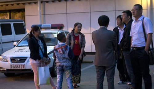 Relatives of Chinese passengers onboard the missing Malaysia Airlines Flight 370 (left) talk to Chinese officials (right) outside a hotel as the Malaysia Airlines ceased to provide the hotel accommodation for the relatives in Beijing on May 2, 2014. /AP