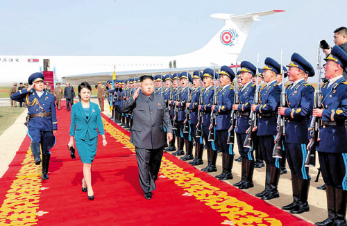 North Korean leader Kim Jong-un and his wife Ri Sol-ju inspect an honor guard at an air base in this picture published on Saturday by the official Rodong Sinmun. /News 1