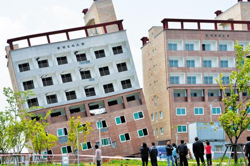 People watch twin buildings in Asan, South Chungcheong Province after one of them tilted sideways on Monday.
