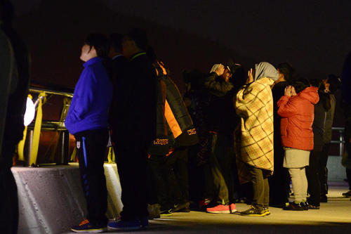 Families of missing passengers from the ferry disaster off the southwest coast cry as they watch the dark sea at a port in Jindo, South Jeolla Province on Tuesday. /News 1