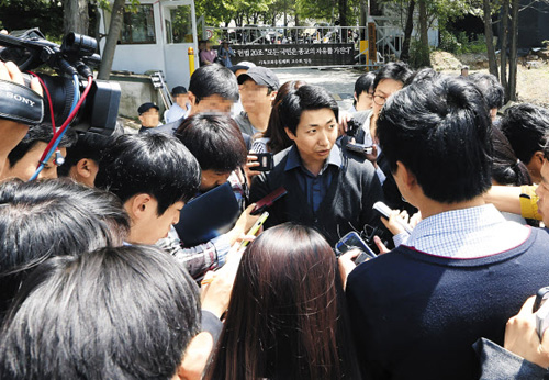 A spokesman for a cult led by ferry owner Yoo Byung-eon is surrounded by reporters at the sects compound in Anseong, Gyeonggi Province on Wednesday.