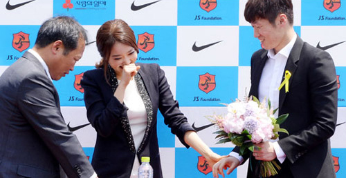 Park Ji-sung receives a bouquet of flowers from his fiancée Kim Min-ji. His father can be seen on the left. /News 1