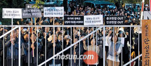 Followers of cult leader and ferry owner Yoo Byung-eon rally at a compound in Anseong, Gyeonggi Province on Tuesday, holding placards that claim they are victims of religious persecution.
