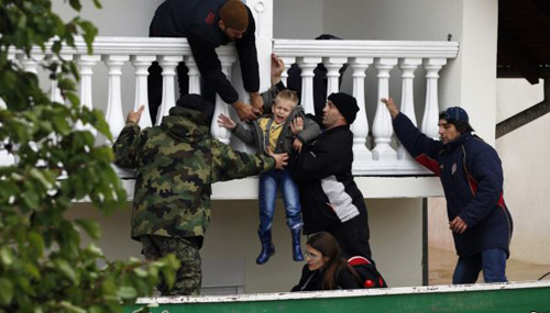 Serbian army soldiers evacuate a boy from a flooded house in the town of Obrenovac, southwest of Belgrade, Serbia, on May 17, 2014. /Reuters
