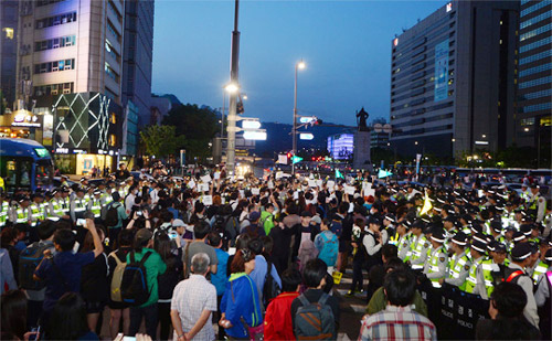Protesters confront the police on their way to Cheong Wa Dae after a rally in memory of the victims of the ferry disaster in Cheonggye Plaza, Seoul on Sunday. /Newsis