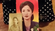 A container holding the remains of Pak Kyung-jae, along with a photo of her.