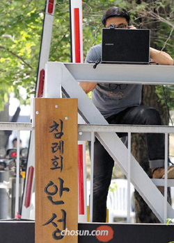 A cult follower sets up a webcam on Monday to monitor police movements at the entrance of a compound owned by the sect led by ferry owner Yoo Byung-eon.