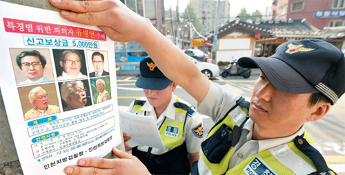 A police officer posts a most-wanted flyer for Yoo Byung-eon, the de facto owner of ferry operator Chonghaejin Marine, in Jongno, Seoul on Thursday. /News 1