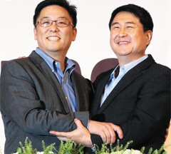 Daum CEO Choi Sae-hoon and Kakao co-CEO Lee Sirgoo pose at a press conference in Seoul on Monday.