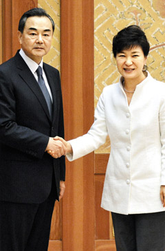 President Park Geun-hye shakes hands with Chinese Foreign Minister Wang Yi at Cheong Wa Dae in Seoul on Monday. /Newsis