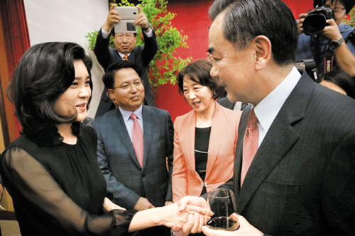 Samsung chairman Lee Kun-hee's daughter Lee Boo-jin shakes hands with Chinese Foreign Minister Wang Yi at an event in Seoul on Tuesday.
