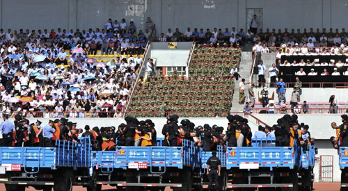 Trucks carrying criminals and suspects are seen during a mass sentencing rally at a stadium in Yili, Xinjiang, Uighur Autonomous Region on May 27, 2014. /Reuters