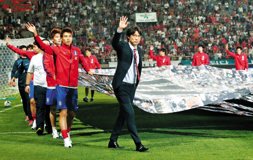 Manager Hong Myung-bo and players celebrate their participation in the 2014 FIFA World Cup in Brazil, after a friendly match against Tunisia at Seoul World Cup Stadium on Wednesday.