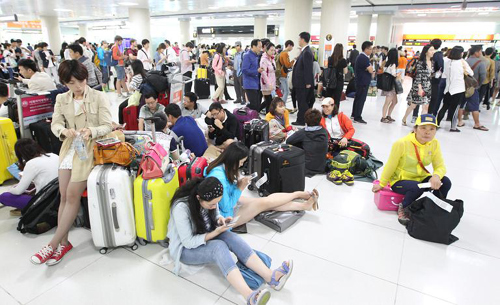 Tourists are stranded at Jeju Airport as flights are canceled due to strong winds on the island on Monday. /Newsis