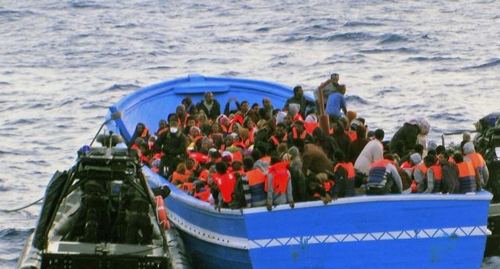 In this photo released by the Italian Navy on May 22, 2014, a fishing boat filled with migrants receives aid from an Italian Navy motor boat. /AP