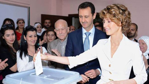 A handout picture released by the official Facebook page of Syrias First Lady Asma al-Assad shows Syrian President Bashar al-Assad (center) watching on as his wife Asma casts her vote at a polling station in Maliki. /AFP