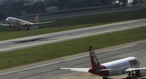 Brazilian airline GOLs Boeing 737-800 aircraft (left) takes off near TAMs Airbus A320 aircraft at Congonhas airport, São Paulo on Jan. 17, 2014. /Reuters