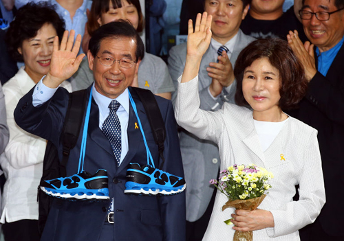 Seoul mayor-elect Park Won-soon waves with his wife to supporters after his victory at his office in Seoul on Thursday morning.